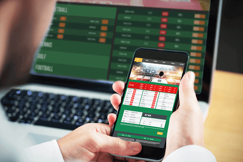 sports betting platform on phone and laptop
